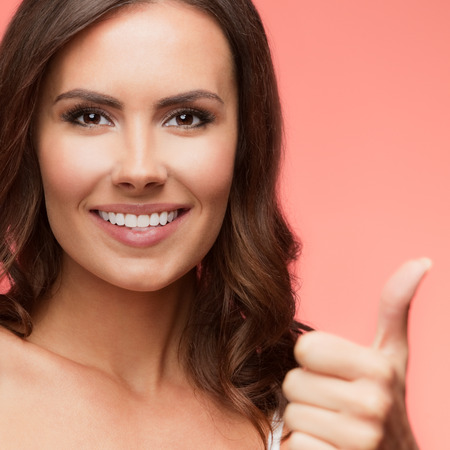 red haired girl: Portrait of cheerful smiling young woman showing thumb up gesture, over light red background Stock Photo