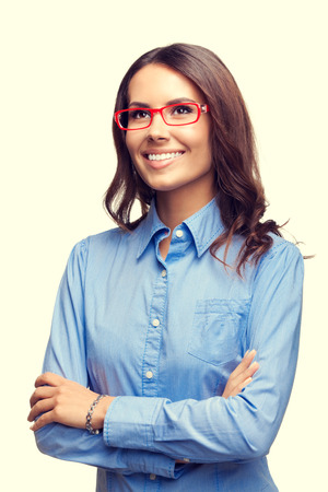 ejecutivo en oficina: Retrato de joven empresaria sonriente en vidrios rojos mirando hacia arriba, en plantean los brazos cruzados