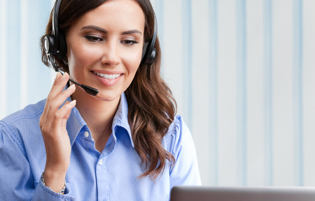 sales agent: Portrait of happy smiling cheerful beautiful young female support phone operator in headset, at office, with blank copyspace area for slogan or text. Customer assistance service concept. Stock Photo