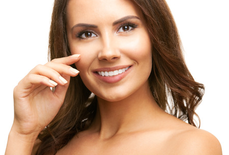 mooie vrouwen: Portrait of happy smiling beautiful young brunette woman touching skin or applying cream, isolated over white background