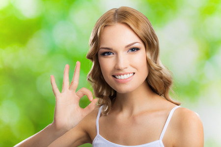 allright: Portrait of beautiful young happy smiling blond woman with okay gesture, outdoors Stock Photo