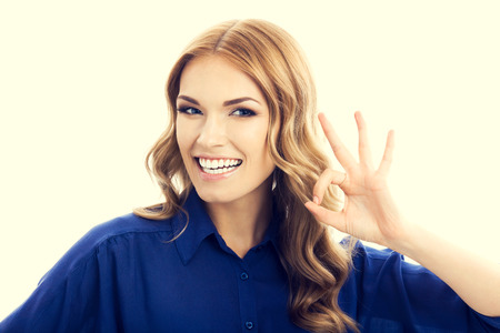 Happy smiling businesswoman in blue clothing showing okay hand sign gesture Stock Photo