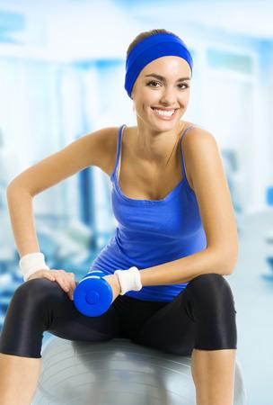 ropa deportiva: Joven mujer feliz en ropa deportiva azul haciendo ejercicio con bola de pilates y mancuernas, en el club de fitness o centro. Belleza y el concepto de salud.