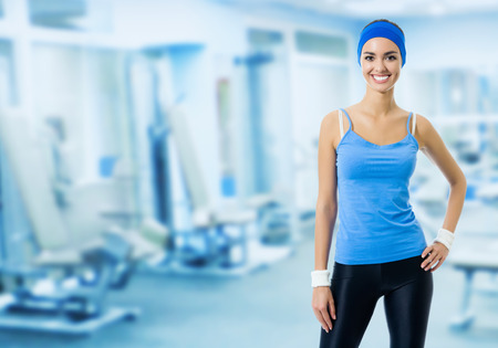 blank center: Portrait of young happy smiling woman in blue sportswear, at fitness club or center, with blank copyspace area for slogan or text message. Beauty and health concept.