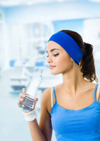 water sports: Young woman in blue sportswear drinking water from bottle, at fitness club or center, with blank copyspace area for slogan or text message. Beauty and health concept.