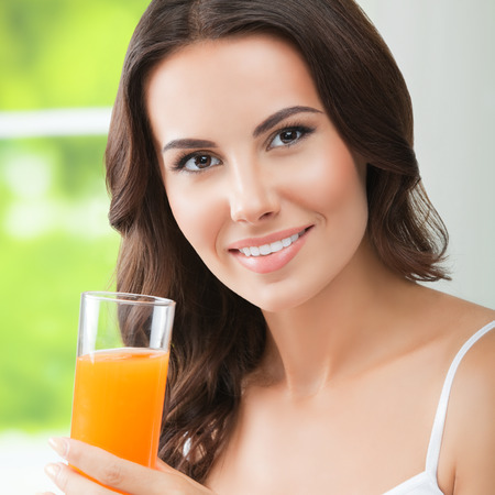 brunette woman: Portrait of happy smiling young beautiful brunette woman drinking orange juice. Healthy eating, beauty and dieting concept. Stock Photo