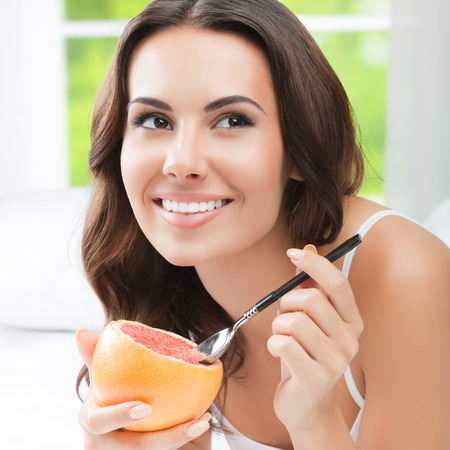 brunette woman: Cheerful smiling brunette woman eating grapefruit at home. Healthy eating, beauty and dieting concept. Stock Photo