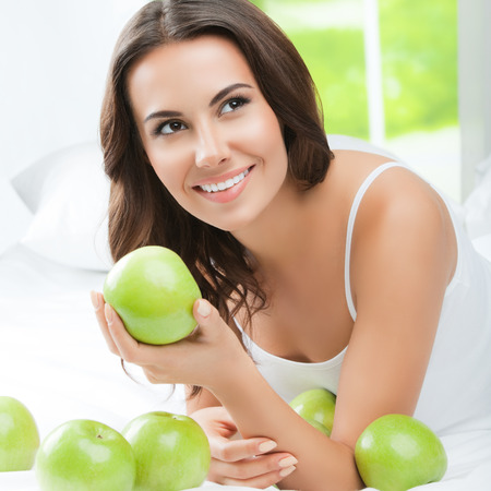 green apples: Young happy smiling brunette woman with green apples, indoors. Healthy eating, beauty and dieting concept. Stock Photo