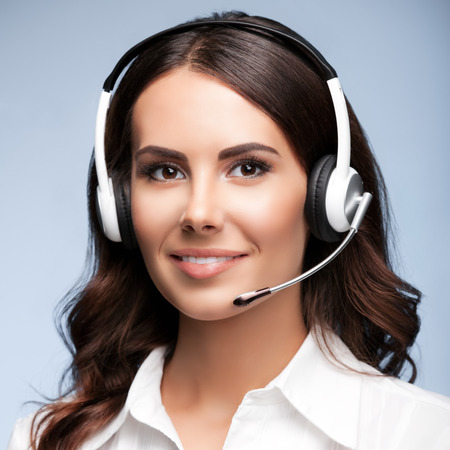 Female customer support phone operator in headset, against grey background. Consulting and assistance service call center.