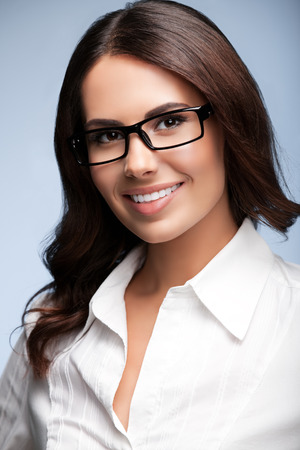 business attire teacher: Portrait of happy smiling young brunette businesswoman in glasses, over grey background