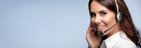 operador de telefonía de atención al cliente en auriculares, con área de copyspace en blanco para lema o mensaje de texto, sobre fondo gris. Servicio de consultoría y asistencia call center. Foto de archivo