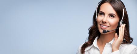サポート女性の電話オペレーターのヘッドセットに灰色の背景上のスローガンまたはテキスト メッセージを空白の copyspace エリアが見上げるの肖像