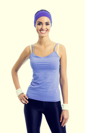 beauty and health: Portrait of smiling sporty brunette woman in violet sportswear. Young female fitness instructor or personal trainer at studio shot. Health, beauty and fitness concept. Stock Photo