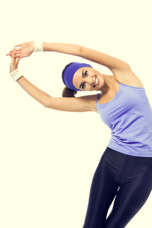 beauty and health: Happy smiling woman in violet sportswear doing stretching exercise or youga moves. Young sporty dark-haired model at studio shot. Health, beauty and fitness concept.