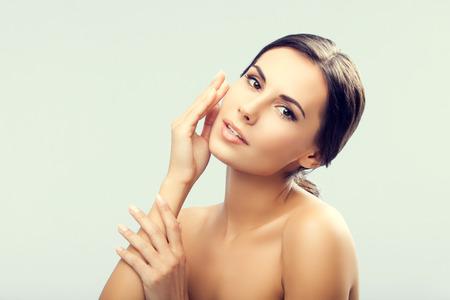 naked young women: Портрет счастливой улыбкой красивая молодая женщина, касаясь кожи или применения крема Фото со стока