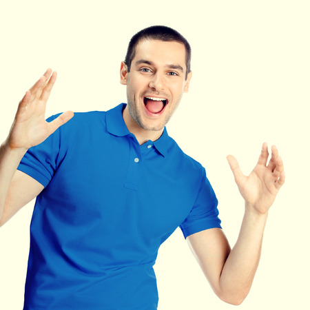 surprised man: Portrait of expressive happy surprised gesturing young handsome man in blue casual t-shirt clothing, looking at camera, specialy toned Stock Photo