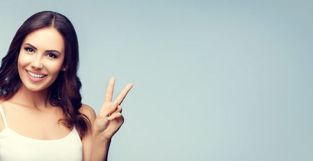 2 persons only: Portrait of beautiful young woman showing two fingers or victory gesture, with blank copyspace area for text or slogan