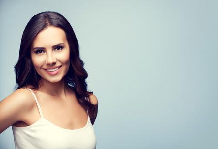 eslogan: Retrato de la hermosa mujer joven alegre sonriente, con �rea de copyspace blanco para el texto o lema Foto de archivo