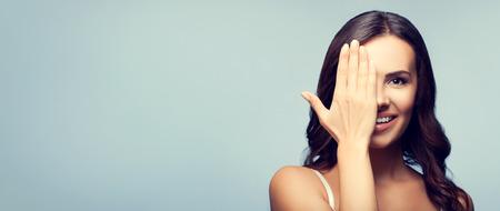 sorprendido: Foto del concepto de feliz sonriente mujer joven con un ojo cerrado a mano, que cubre parte de su rostro, con área de copyspace blanco para el texto o lema Foto de archivo
