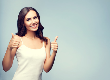 Portrait of beautiful cheerful smiling young woman showing thumb up gesture, with blank copyspace area for text or slogan
