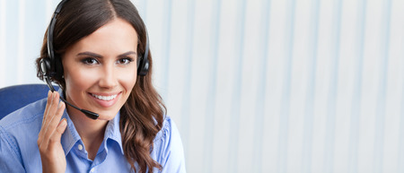 Portrait of happy smiling cheerful beautiful young female support phone operator in headset, at office, with blank copyspace area for slogan or text. Customer assistance service concept. Stockfoto