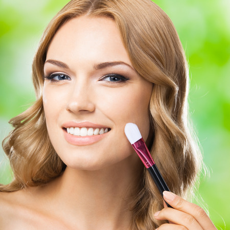 Portrait of young smiling lovely blond woman with make up brush, outdoors. Visage and cosmetics concept.