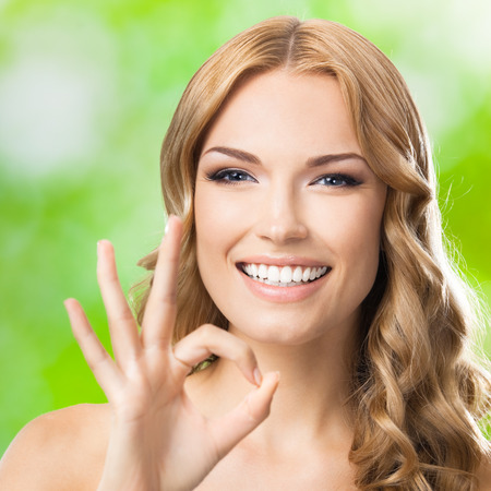 blondy: Portrait of beautiful young happy smiling lovely blond woman with okay gesture, outdoors