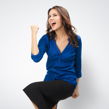 posing  agree: Happy gesturing young cheerful gesturing businesswoman, posing at studio against grey background Stock Photo