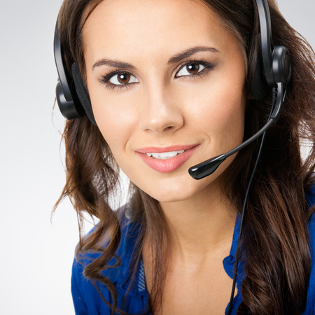 customer support: Portrait of happy smiling young support phone operator or businesswomen in headset, posing at studio against grey background