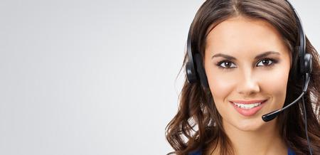 Porträt der glücklich lächelnde junge Unterstützung Telefonistin oder Geschäftsfrauen in Headset, mit leeren Copyspace Bereich für Slogan oder Text, posiert im Studio vor grauem Hintergrund Standard-Bild