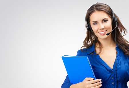 Portrait of happy smiling cheerful beautiful young support phone operator in headset with blue folder, with blank copyspace area for slogan or text, posing at studio against grey background Standard-Bild