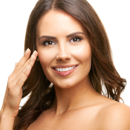 beautiful background: Portrait of happy smiling beautiful young brunette woman touching skin or applying cream, isolated over white background