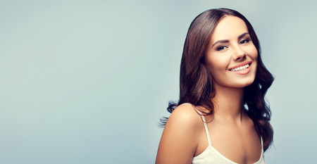 Portrait of beautiful happy smiling young brunette woman, with blank copyspace area for text or slogan