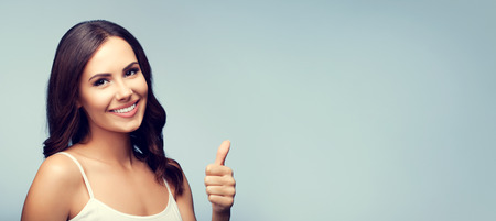 Portrait of beautiful smiling young brunette woman showing thumb up gesture, with blank copyspace area for text or slogan