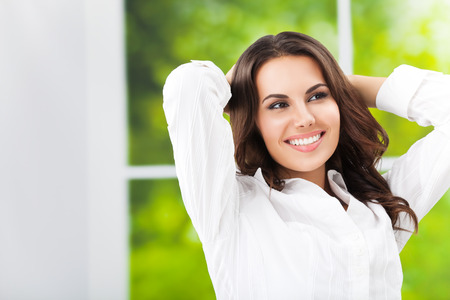 raised arms: Young happy smiling attractive brunette businesswoman with raised arms, at office, with blank copyspace area for slogan or text Stock Photo