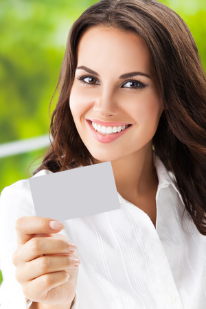 debet: Happy smiling brunette businesswoman showing blank business or plastic card with copyspace area for slogan or text. Invitation concept.