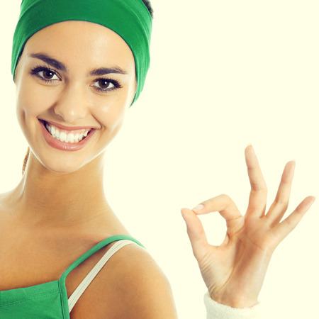 hand wear: Portrait of smiling young brunette woman in green fitness wear showing ok hand sign