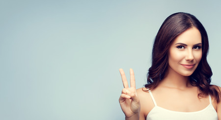 2 persons only: Portrait of young lovely brunette woman showing two fingers or victory gesture, with blank copyspace area for text or slogan