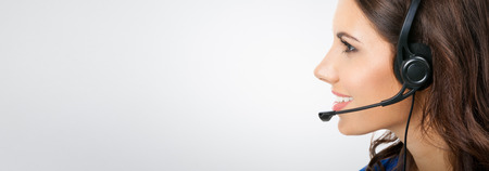 Profile view of smiling young support phone operator or businesswomen in headset