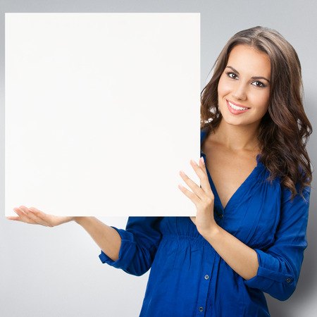 Portrait of smiling young woman, showing blank signboard with blank copyspace area for slogan or text, posing at studio against grey background