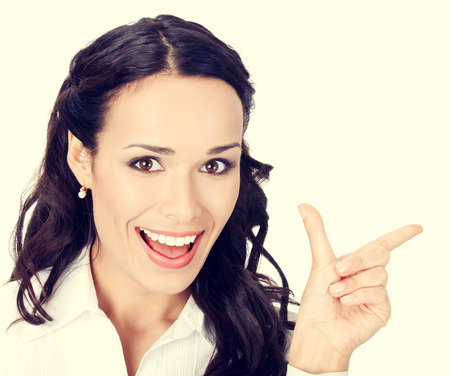 copyspase: Happy smiling young businesswoman showing blank area for sign or copyspase