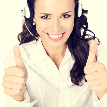 happy businesswoman: Portrait of happy smiling cheerful customer support phone operator or businesswoman in headset showing thumbs up hand sign gesture Stock Photo