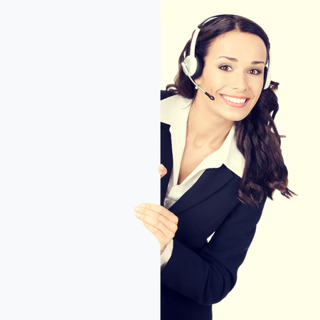 Cheerful young customer support phone operator or businesswoman in headset showing blank signboard