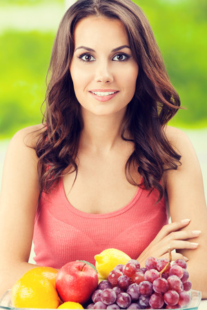 brunette woman: Young happy smiling brunette woman with plate of fruits, outdoors