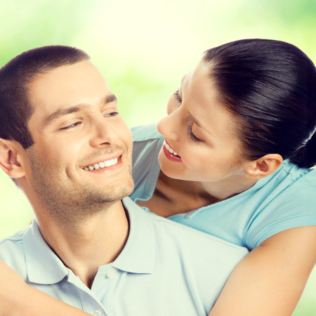 young couple smiling: Portrait of young happy smiling embracing lovely couple, looking at each other, outdoors Stock Photo