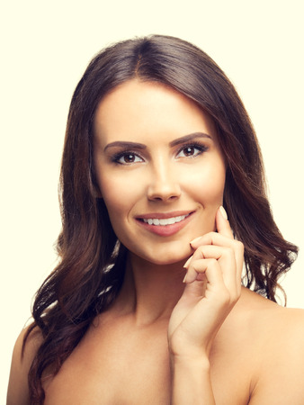 pretty brunette woman: Portrait of happy smiling beautiful young brunette woman touching skin or applying cream Stock Photo