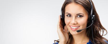 幸せな若い笑顔の肖像画がスローガンまたは灰色の背景に対してスタジオでポーズのテキストを空白の copyspace エリアと、ヘッドセットで電話演算子 写真素材