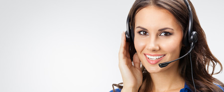 Portrait of happy smiling young support phone operator or businesswomen in headset, with blank copyspace area for slogan or text, posing at studio against grey background