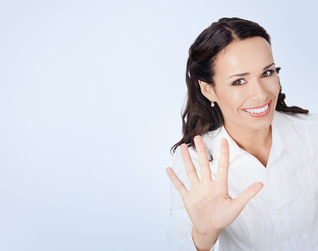 five fingers: Happy smiling young businesswoman in white business style clothing, showing five fingers, with blank copyspace area for slogan or text message Stock Photo
