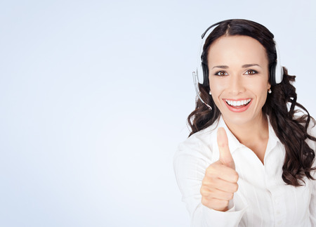 thumbsup: Portrait of happy smiling cheerful customer support phone operator in headset showing thumbs up gesture in white business style clothing, with blank copyspace area for slogan or text message
